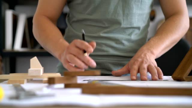 vidéos et rushes de charpentier, régimes de dessin à son bureau de travail. - designer