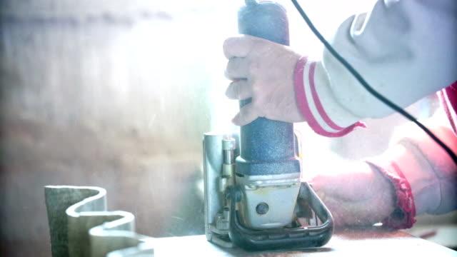 Tischler Bohren Löcher in einer Sperrholz Bord.