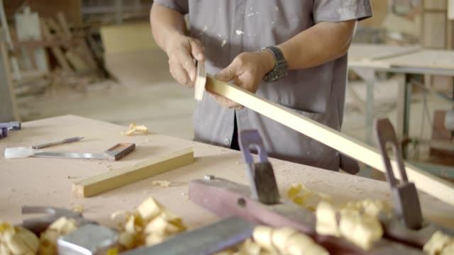 vidéos et rushes de charpentier pendant le travail à l'atelier de bois. - tape measure