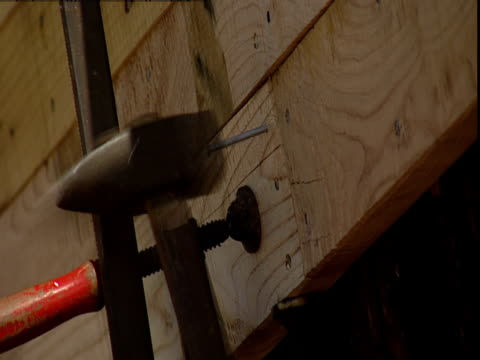 a carpenter hammers a nail into wood. - hammer stock videos and b-roll footage