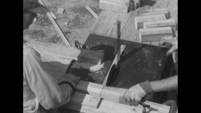 carpenter in a sleeveless undershirt nailing a board / two men quickly cutting 2x4s into small segments on a table saw / vs a group of carpenters... - plank stock videos & royalty-free footage