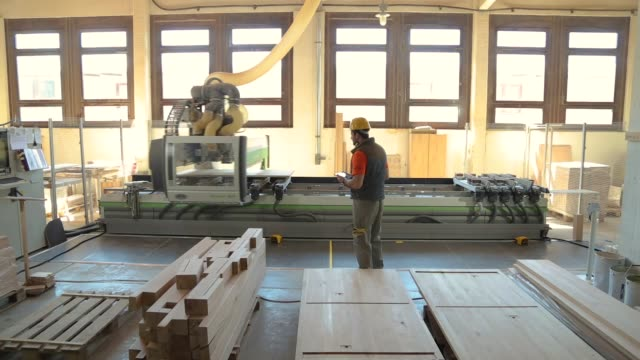carpenter in wood factory, using a digital tablet, checking results of circular saw machine in furniture factory, wearing safety equipment - manufacturing machinery stock videos & royalty-free footage