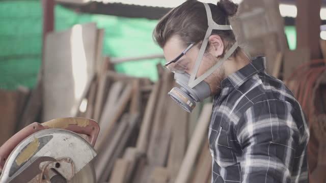 大工は木を切っている - 材木置き場点の映像素材/bロール