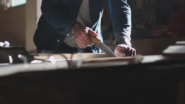 Carpenter is sawing wood with hand saw