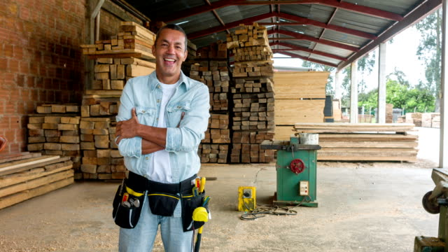 Carpenter looking happy at his carpentry
