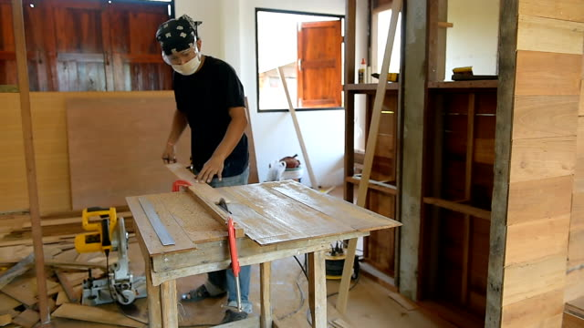 carpenter man use a circular saw table for cut wood plank