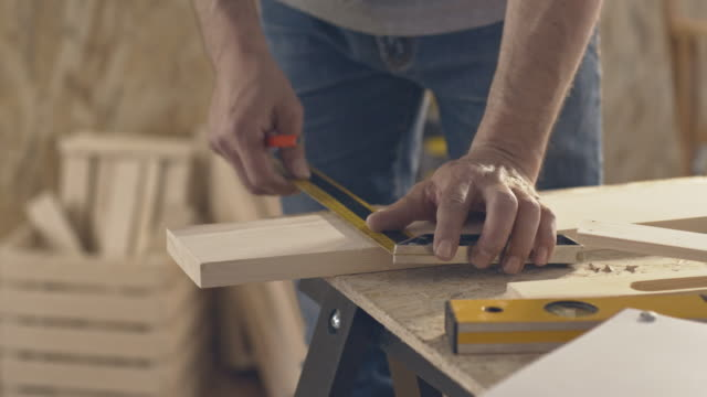 carpenter marking wooden plank, using pencil and ruler - work tool stock videos & royalty-free footage