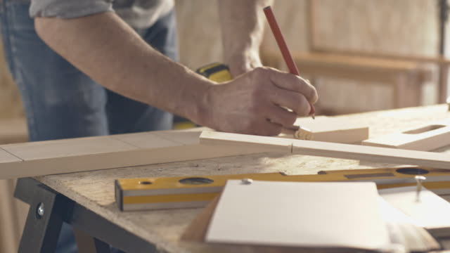 Carpentiere di misura e marcatura un pezzo di legno
