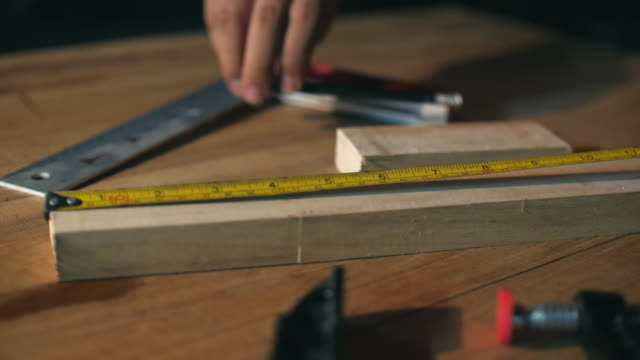 Carpenter Measuring and Marking Wood Beam in Workshop