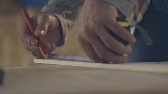 carpenter measuring and marking wood block - workbench stock videos & royalty-free footage