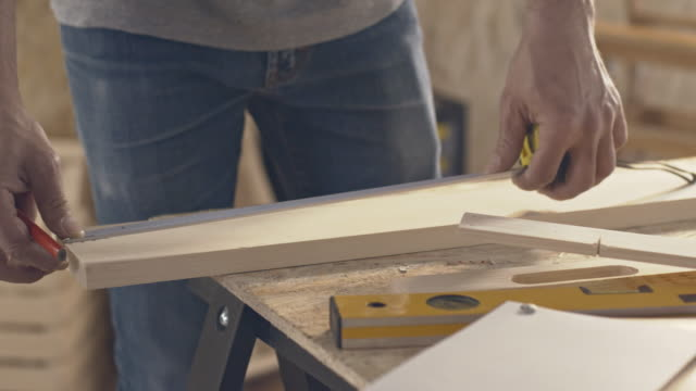 Carpenter measuring and marking wooden plank