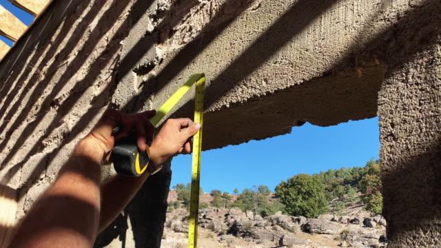 vidéos et rushes de un charpentier mesurant l'ouverture d'une fenêtre - parpaing