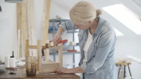 4k: snickare målning möbler i hennes verkstad. - lämplighet bildbanksvideor och videomaterial från bakom kulisserna