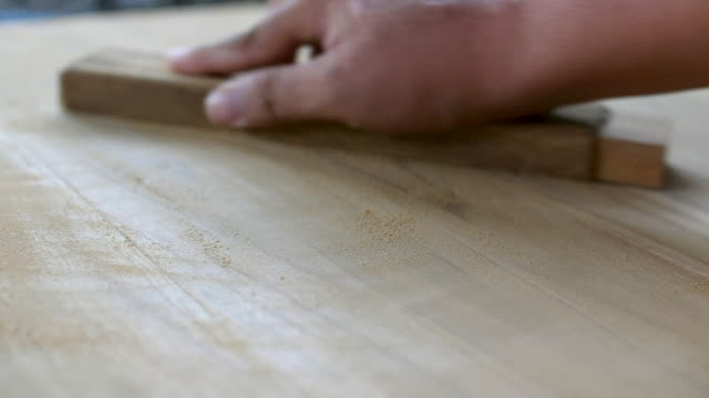 carpenter polishing wood table with sand paper with nature sunlight - sand paper stock videos and b-roll footage