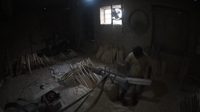 a carpenter rough shapes willow blades into cricket bats in a factory on june 08 2019 in halmullah 50 km south of srinagar the summer capital of... - クリケットバット点の映像素材/bロール