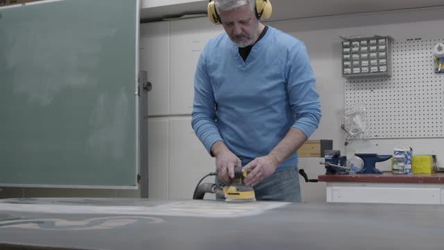 vídeos de stock, filmes e b-roll de carpinteiro lixando uma mesa - protetor de ouvido