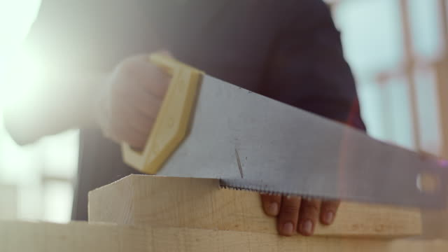 carpenter sawing a plank with a hand wood saw at construction site - home improvement stock videos & royalty-free footage
