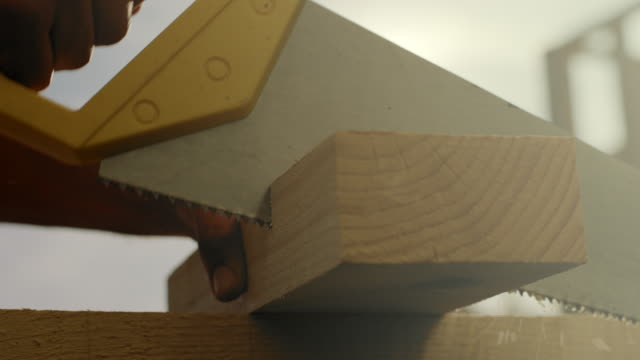 carpenter sawing a plank with a hand wood saw at construction site - building activity stock videos & royalty-free footage