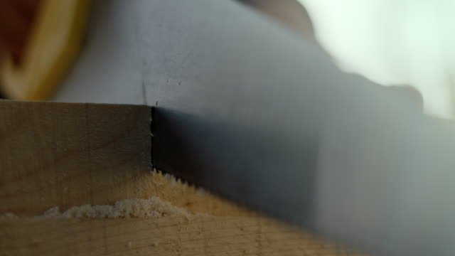 carpenter sawing a plank with a hand wood saw at construction site - sawdust stock videos and b-roll footage