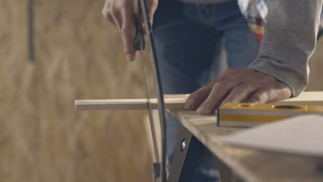 Carpenter sawing wood with hand saw