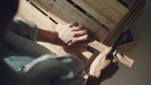 vídeos de stock, filmes e b-roll de carpinteiro serrar madeira com serrote - conveniência