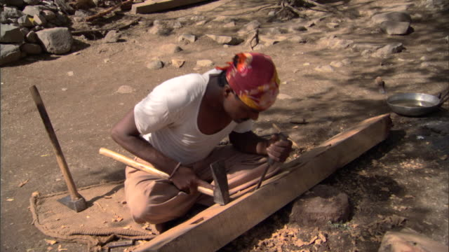 WS Carpenter seated on ground driving holes into wooden beam, Pune, Maharashtra, India