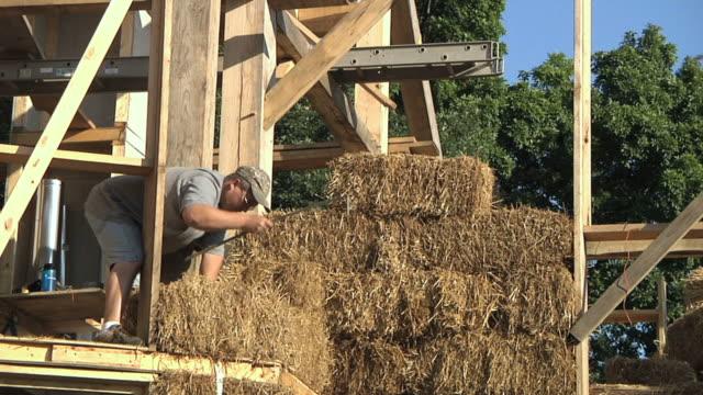 vídeos de stock, filmes e b-roll de ws zo carpenter stitching bales of straw during framing of an energy efficient post / grass lake, michigan, usa  - ponto de costura