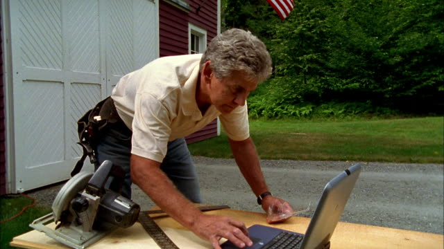A carpenter stops his project to check his laptop for directions.