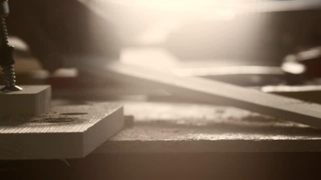 vidéos et rushes de menuisier prenant un morceau de bois de la table - atelier d'artisan