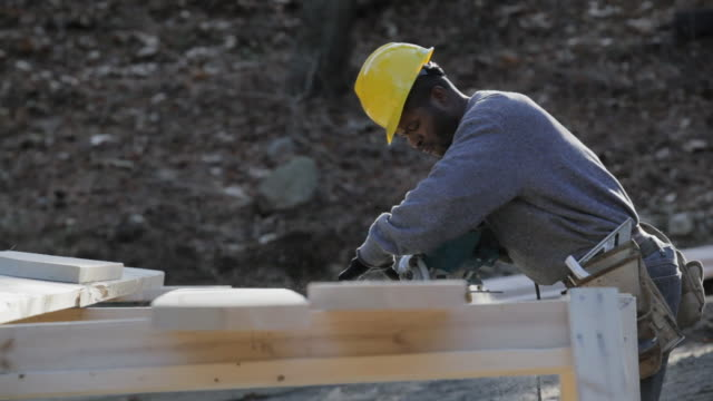 A carpenter uses a circular saw for a bevel cut on a dormer rafter.