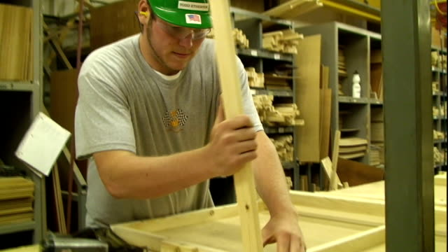 a carpenter uses a nail gun as he secures two supports on a square piece of wood. - tavolo video stock e b–roll