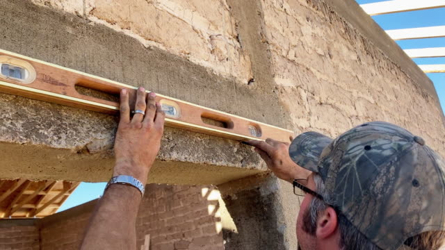 a carpenter using a level in a door or window frame of a building under construction - measuring stock videos & royalty-free footage