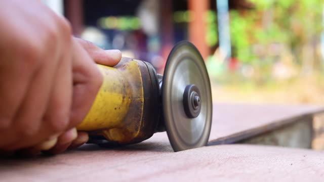 vídeos de stock, filmes e b-roll de carpenter using circular saw cutting wooden boards with hand power tools. - serra circular