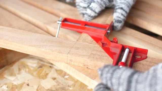 vídeos y material grabado en eventos de stock de carpintero con abrazadera de la esquina en pedazos de madera, primer plano y dolly shot - herramienta de mano