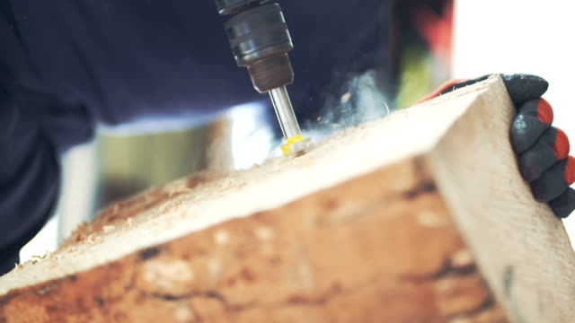 Carpenter Using Drill Machine On Wood
