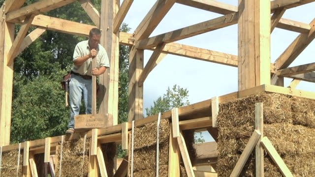 ws zo carpenter using large mallet to level beams above bales of straw during framing of an energy efficient post / grass lake, michigan, usa          - mallet hand tool stock videos and b-roll footage
