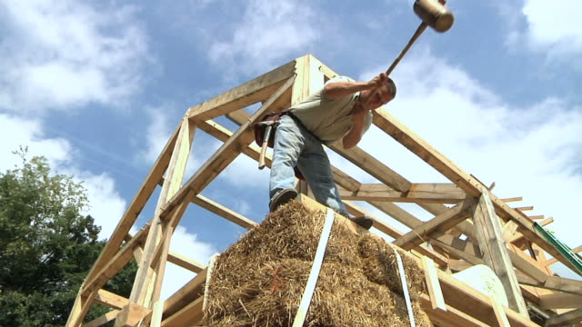 ws carpenter using large mallet to position bales of straw during framing of an energy efficient post / grass lake, michigan, usa - mallet hand tool stock videos and b-roll footage