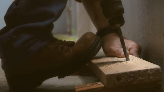 slo mo carpenter using on electric drill on splat wood - construction material stock videos & royalty-free footage