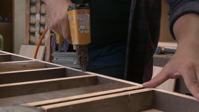 vídeos de stock e filmes b-roll de carpenter using staple gun - one mid adult man only