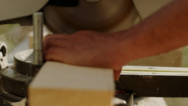 Carpenter using tablesaw to cut some plank