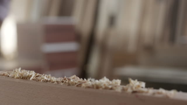 Carpenter wiping sawdust of the wooden plank