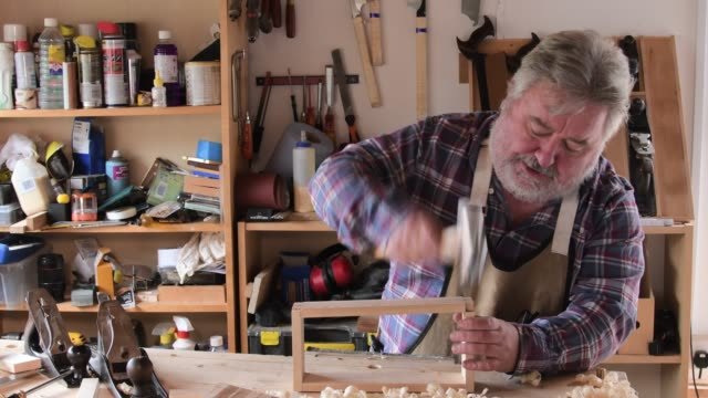 carpenter working in workshop hammering joint - bricolage video stock e b–roll