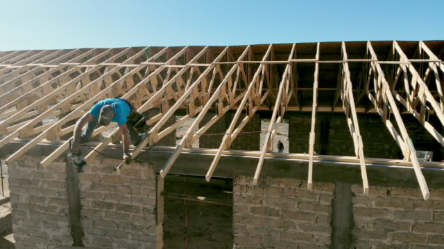 a carpenter working on the roof of a new building - construction worker stock videos & royalty-free footage