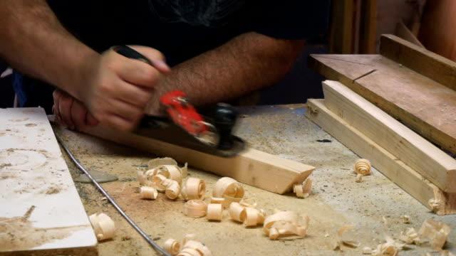 Carpenter working, using plane to level wood profile