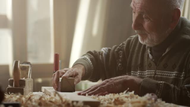 vídeos y material grabado en eventos de stock de carpintero trabajando con papel de lija - bricolaje