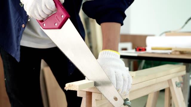 vídeos de stock, filmes e b-roll de carpinteiro trabalhando com serra e prancha de madeira na oficina - serra circular