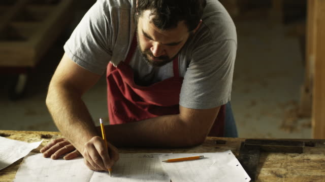 carpenter writing down notes on sheets of paper and in a book - craftsperson stock videos & royalty-free footage
