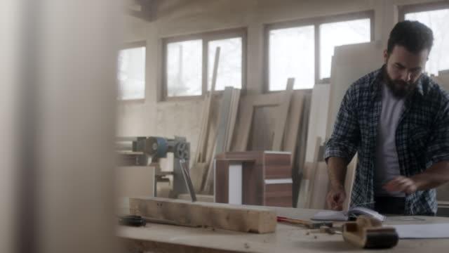 vídeos y material grabado en eventos de stock de measurments de escritura en la oficina de carpinteros del carpintero - carpintería