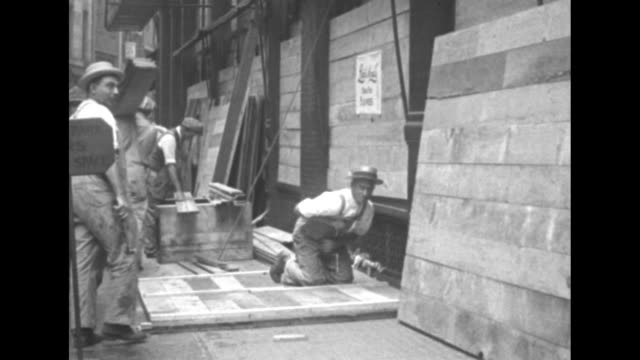 carpenters wearing overalls work at boarding up store windows during the police strike in boston / note: exact day not known - timber stock videos & royalty-free footage