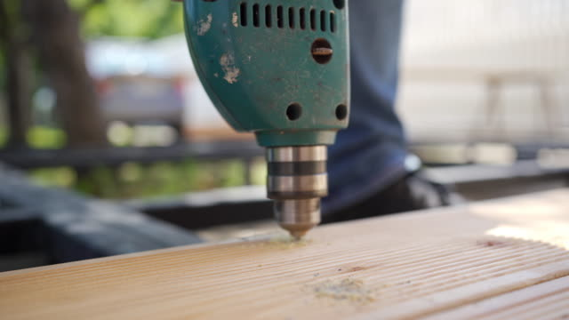 carpentry professional worker drilling a hole in a wooden plank - wood stock videos & royalty-free footage